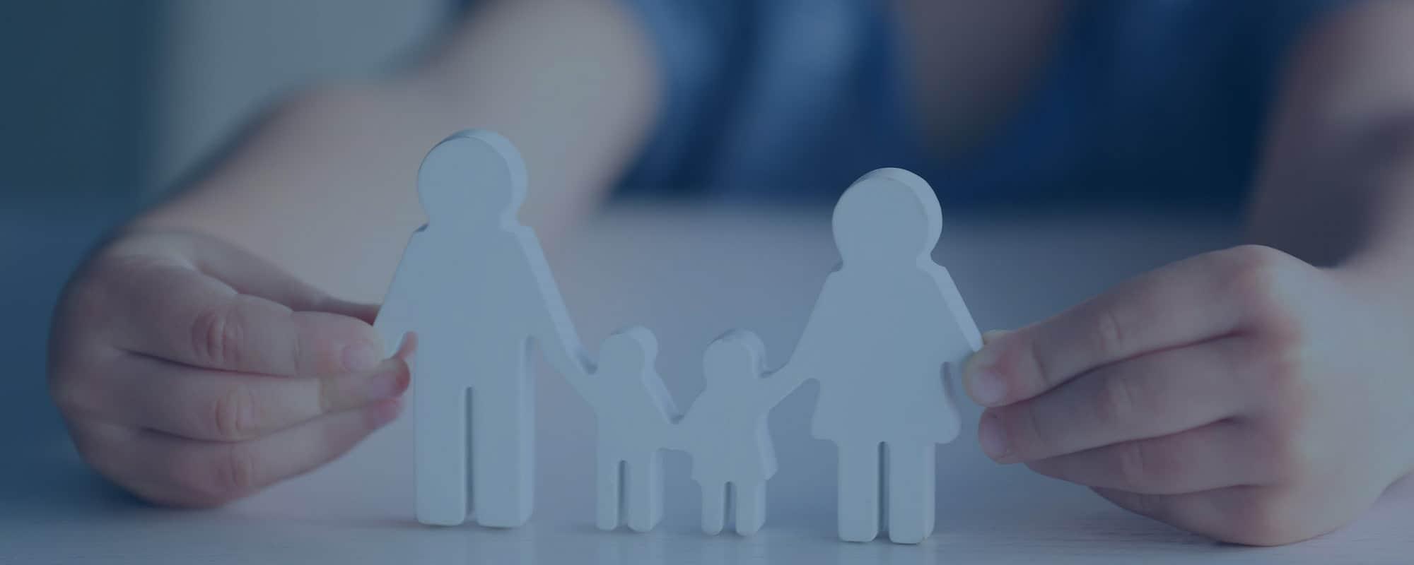 Familienrecht. Kind hält Familienfiguren aus Holz geschnitzt in Händen
